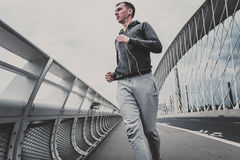 Young man running on the modern bridge in the city, listening music on smartphone Royalty Free Stock Photography