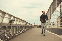 Young man running on the modern bridge in the city, listening music on smartphone Stock Photo