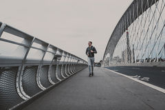 Young man running on the modern bridge in the city, listening music on smartphone Royalty Free Stock Photos