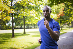 Young man running outdoors Royalty Free Stock Images