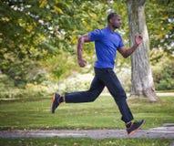 Young man running outdoors Stock Photos