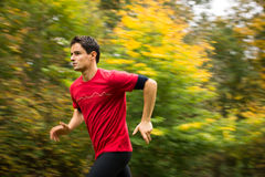 Young man running outdoors in a city park on a fall/autumn day. (motion blurred image stock image