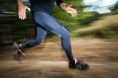 Young man running outdoors in a forest, going fast. Motion blurred image Stock Photography