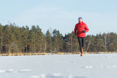 Young man running outdoors in winter snowy sunny forest Royalty Free Stock Images