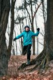 Young man running outdoors during workout in a forest among leaf Royalty Free Stock Image