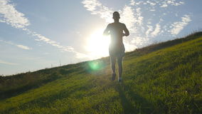 Young man running over green hill over blue sky background. Male athlete is jogging in nature at sunset. Sports runner stock footage