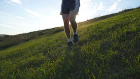 Young man running over green hill over blue sky background. Male athlete is jogging in nature at sunset. Sports runner stock video footage