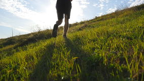 Young man running over green hill over blue sky background. Male athlete is jogging in nature at sunset. Sports runner. Jogging uphill outdoor at sunrise with stock footage