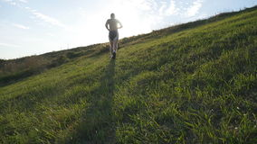 Young man running over green hill over blue sky background. Male athlete is jogging in nature at sunset. Sports runner. Jogging uphill outdoor at sunrise with stock video