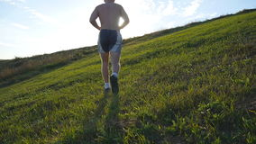 Young man running over green hill over blue sky background. Male athlete is jogging in nature at sunset. Sports runner stock video