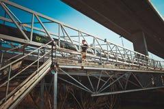 Young man running over metal bridge Stock Photo