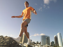 Young man running over rocks outdoors, low angle view Stock Photos