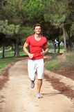 Young man running through park Stock Photo