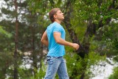 Young man running through park Stock Photography