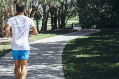 Young man running through park Royalty Free Stock Photography