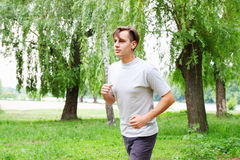 Young man running in the park Stock Photos