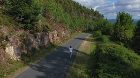 Young man running on the park road. View from drone stock footage