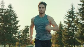 Young man running in park. Sport man jogging outdoor. Tired runner stop. Young man running in park. Sport man jogging outdoor in slow motion. Tired runner stop stock video