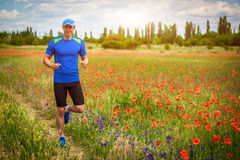 Young man running on poppy field Stock Photos