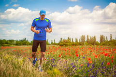 Young man running on poppy field Royalty Free Stock Photos