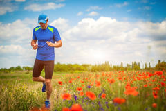 Young man running on poppy field Stock Photo