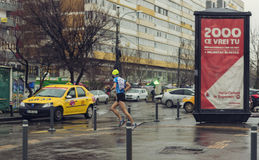 Young man running in the rain on the streets of Bucharest Royalty Free Stock Photo