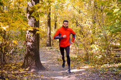Young Man Running on Sunny Trail in the Beautiful Autumn Oak Forest Stock Photo