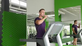 Young man running on treadmill and drinking water stock video
