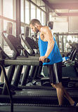 Young man running at treadmill in gym Stock Photos