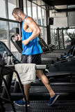 Young man running at treadmill in gym Stock Images