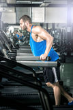 Young man running at treadmill in gym Stock Photo