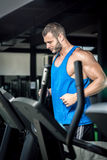 Young man running at treadmill in gym Royalty Free Stock Image
