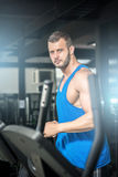 Young man running at treadmill in gym Stock Photography