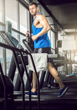 Young man running at treadmill in gym Royalty Free Stock Photography