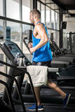 Young man running at treadmill in gym Royalty Free Stock Photo
