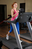 Young man running at treadmill in gym Stock Image