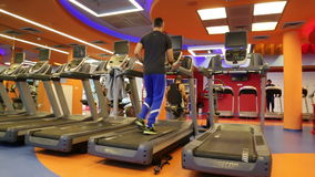 A young man running on a treadmill in a gym stock footage