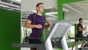 Young man running on treadmill and listening to music on headphones stock video footage