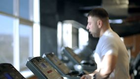 Young man is running on treadmill in sports club. Guy jogs on aerobic machine, holds on to handrail with one hand and looks at display. Handsome male dressed stock video