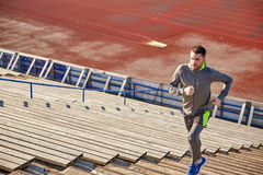 Young man running upstairs on stadium Stock Photo
