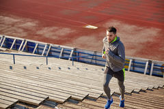 Young man running upstairs on stadium Stock Images