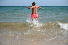 Young man is running in the water of the Black Sea, ready to hav Royalty Free Stock Image