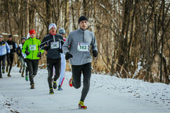 Young man runs ahead of group athletes in winter Park Royalty Free Stock Photos
