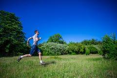 A young man runs along the green grass Royalty Free Stock Photo