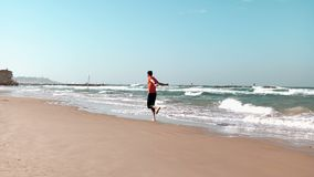 Young man runs along seashore. Summer beach. Freedom concept. European male enjoying holiday vacations. Mediterranean 4K. Bearded guy in orange shirt tries stock video