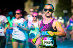Young man runs the Color Vibe 5K race stock photography