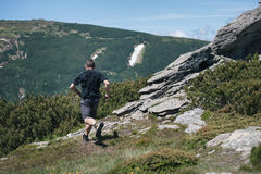 Young man runs in mountains in summertime Royalty Free Stock Images