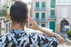 Young man`s backs talking on mobile. Phone outdoors royalty free stock photography