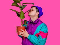 Young man in 90s clothes kissing ficus plant. On pink background stock images