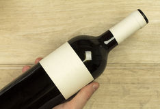 Young man's hand is holding red wine bottle at the light wooden background Royalty Free Stock Images
